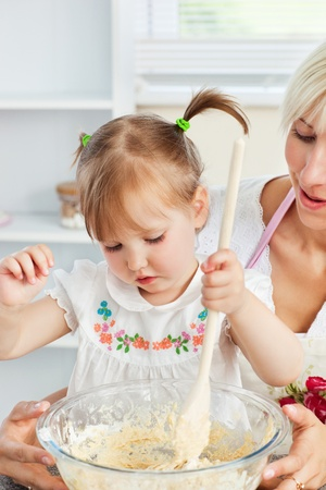 Sweet woman baking cookies with her daughter photo