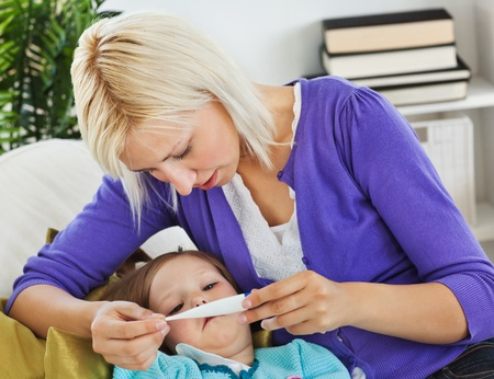 sick day: Mother taking care of her sick child Stock Photo