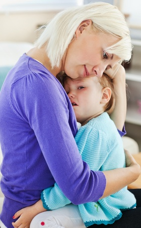 sick girl: Blond woman taking care of her child Stock Photo