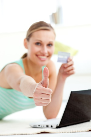 Cute young woman with thumb up holding a card  photo