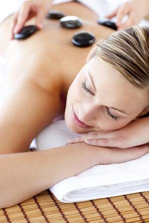 masajes relajacion: Mujer alegra recibir un masaje con piedras calientes