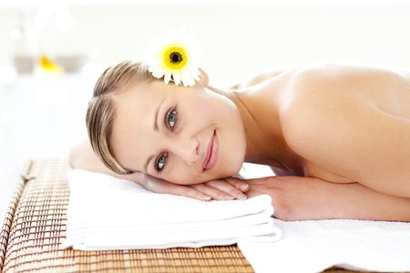 Glowing young woman with flowers in her hair on a massage table Stock Photo - 10247573