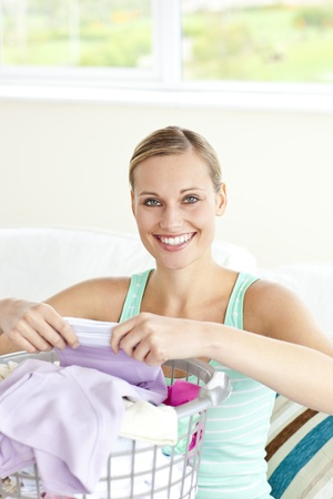 houseclean: Cheerful young woman doing the laundry
