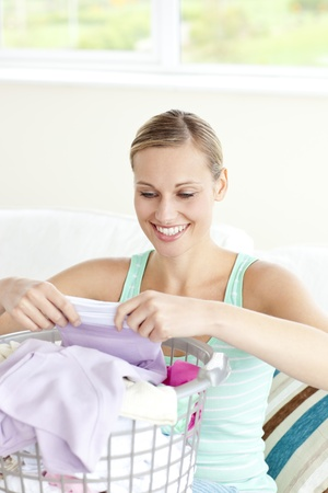 houseclean: Positive young woman doing the laundry  Stock Photo