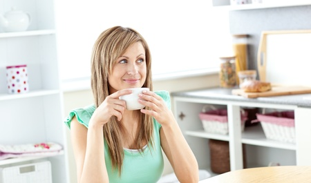 Blond caucasian woman drinking coffee in the kitchen photo