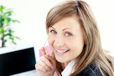 Radiant young businesswoman wearing headphones Stock Photo - 10248766