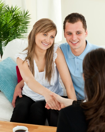 customer relationship: Happy couple concluding a contract with a female dealer