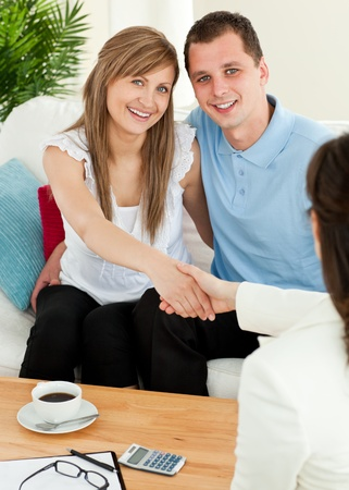 Attractive couple concluding a car contract with a female dealer in the living-room photo