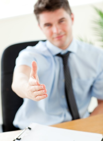 Self-assured businessman reaching his hand to the camera Imagens