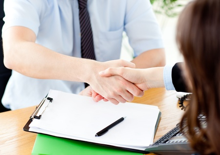conclude: Close up of concluding a contract between businessman and woman