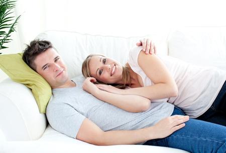 Enamored young couple lyingo together on the sofa  Stock Photo - 10247296