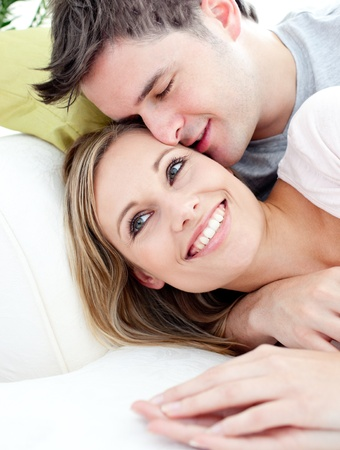 cheek to cheek: Portrait of a loving boyfriend hugging his girlfriend on the sofa in the living roomPortrait of a lo Stock Photo