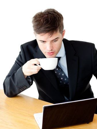 Stressed young businesswoman drinking coffee and using his laptop photo