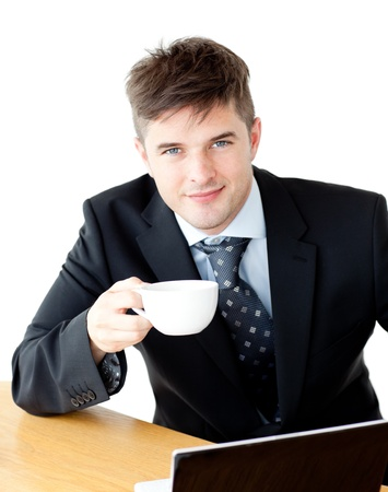 charisma: Charming young businessman holding a cup smiling at the camera