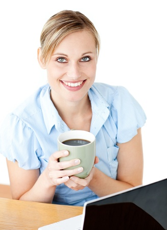 Glowing businesswoman drinking coffee smilng at the camera sitting Stock Photo - 10247930