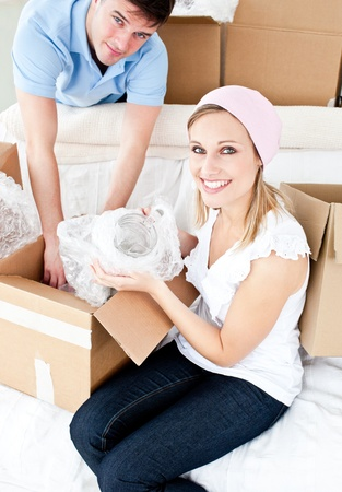 Animated young couple packing a box photo