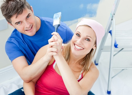 paintrush: Hugging couple having fun while painting a room Stock Photo