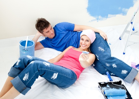 paintrush: Attentive couple relaxing after paiting a room