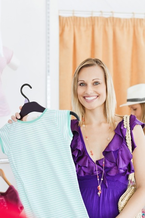 Happy blond woman looking at a shirt in a clothes store  photo