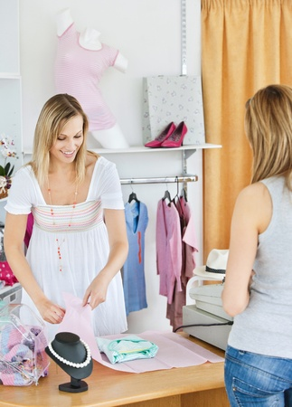 Positive saleswoman packing clothes in a bag   Stock Photo - 10250276