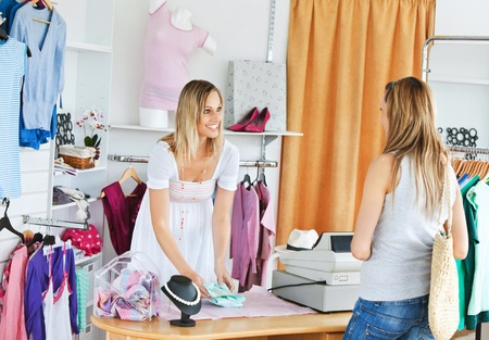 saleswomen: Attractive saleswoman packing clothes in a bag  Stock Photo