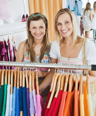 clothing shop: Bright female friends doing shopping smiling at the camera Stock Photo