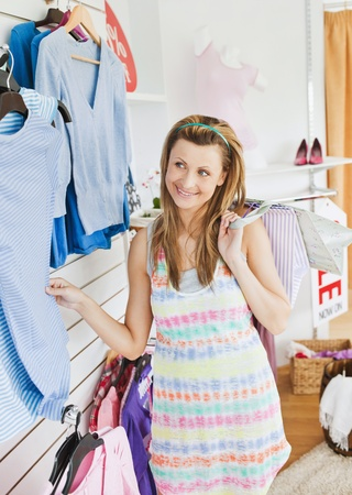 Cute young woman choosing clothes in a shop  photo