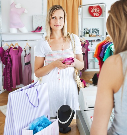 Serious young woman buying clotheslooking at the camera Stock Photo - 10250203