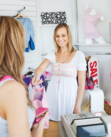people buying: Smiling saleswoman giving clothes to a female customer Stock Photo