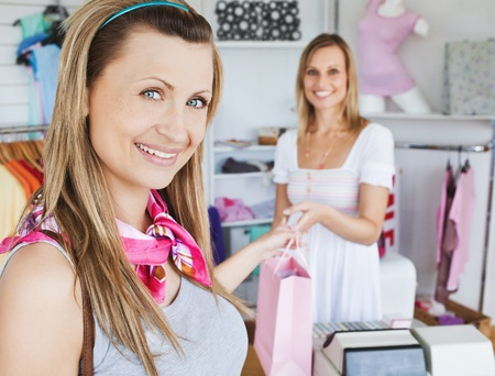 salesperson: Pretty woman taking shopping bag smilig at the camera  Stock Photo