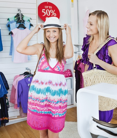 Laughing woman trying a hat with her friend  photo