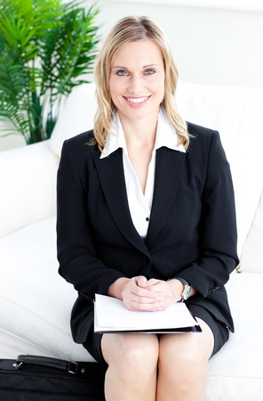 Confident blond businesswoman smiling at the camera sitting on a sofa  photo