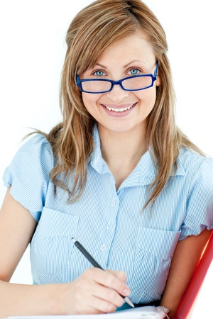 assertive: Ambitious businesswoman taking notes smiling at the camera