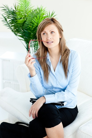 Pensive businesswoman holding glasses sitting on a sofa photo