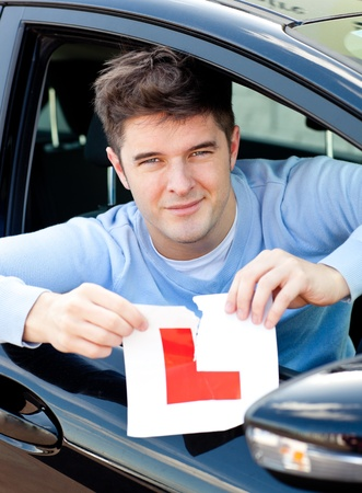 new driver: Happy young male driver tearing up his L sign