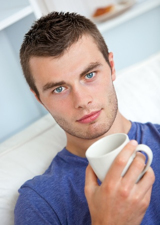 smiling young man: Portrait of a serious young man looking at the camera holding a cup Stock Photo
