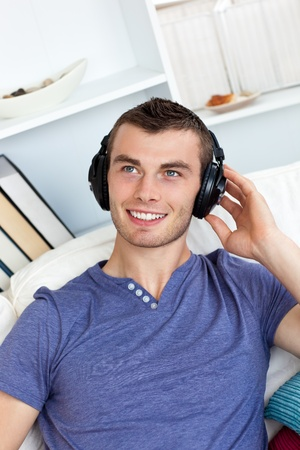 Lively young man listening to music sitting on the couch  photo