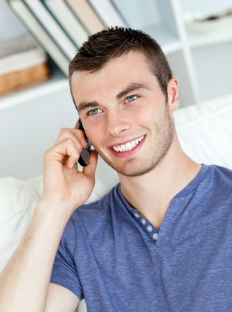 Charismatic young man talking on phone sitting on the sofa  photo