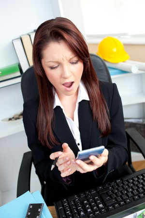 Astonished businesswoman looking at her calculator  photo
