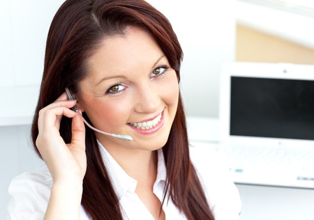representative: Charming young businesswoman wearing headphones smiling at the camera