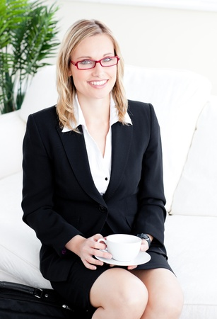 Captivating caucasian businesswoman holding a cup sitting on a sofa  photo