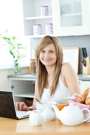 Smiling woman having breakfast in front of the laptop  photo