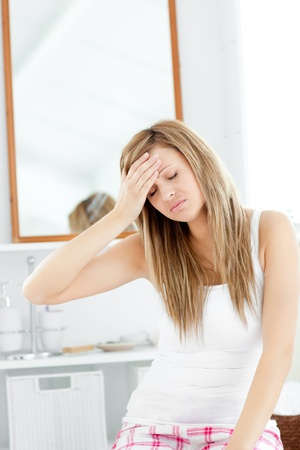 bathroom woman: Dejected woman having a headache sitting in the bathroom
