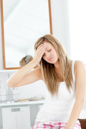 bathroom women: Dejected woman having a headache sitting in the bathroom