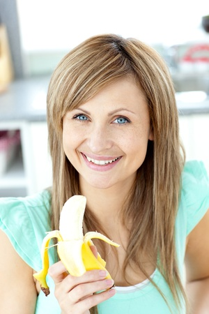 Smiling young holding a banana looking at the camera photo