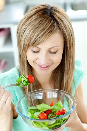 Cute young woman eating a healthy salad in the kitchen  photo