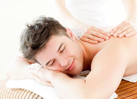 tratamientos corporales: Hombre joven Relaxed que recibe un masaje de espalda Foto de archivo