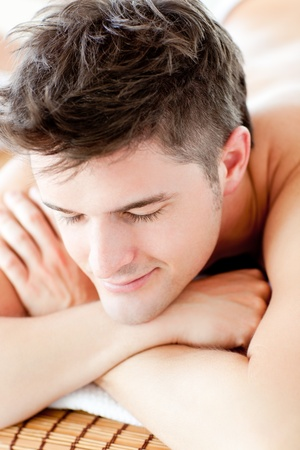 Portrait of a smiling man lying on a massage table  photo