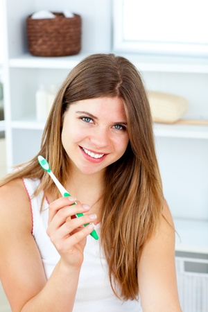 Delighted woman holding a toothbrush smiling at the camera photo