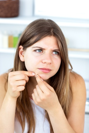 сooking: Unhappy woman with skin irritation cleaning her face Stock Photo